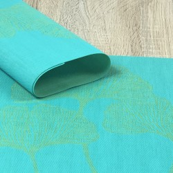 Reverse side of vibrant green Verdigris woven vinyl tablemats rolled up in focus