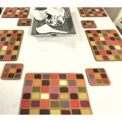 White tablecloth on dining table. Corkbacked funky placemats colourful Harlequin pattern.