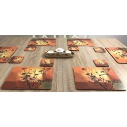 Wooden dining table with Sunset design corkbacked tablemats. Each place mat has stunning orange red brown and yellow colours