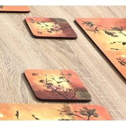 Close up view of Sunset design drinks coasters. Square with soft cork backing against wooden dining table