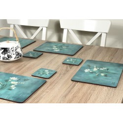 Wooden table with Infinity, teal blue background, corkbacked floral placemats and teapot