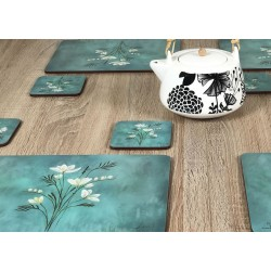 Wooden table with close up of teapot and Infinity, teal blue background, corkbacked floral placemats