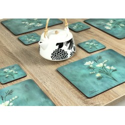 Wooden table with Infinity, teal blue background, corkbacked floral placemats and teapot in centre